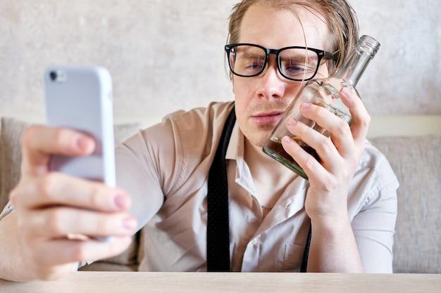 Пьяный мужчина в очках приставляет лицо к бутылке алкоголя и смотрит на смартфон.
