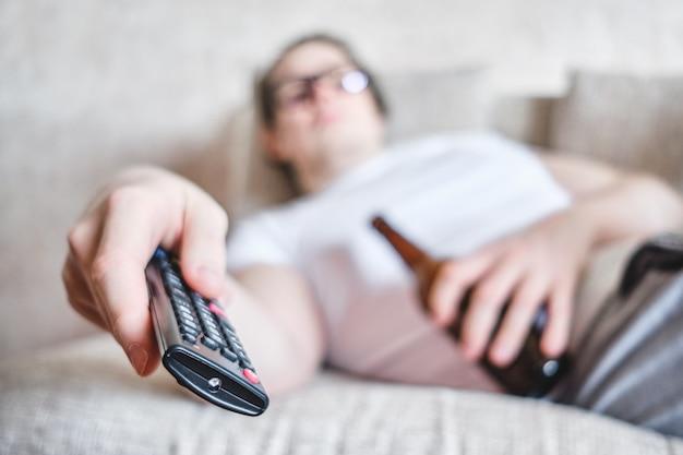 Пьяный мужчина лежит с бутылкой на диване и переключает каналы по телевизору.