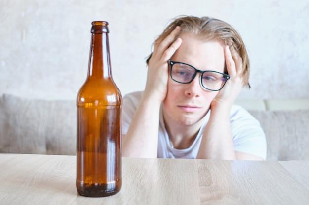 眼鏡をかけた酔っぱらいは、自宅で二日酔いに苦しんでいます。