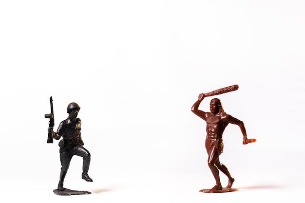 Дуэль между винтажным игрушечным солдатиком и первобытным человеком, изолированным на белом фоне.