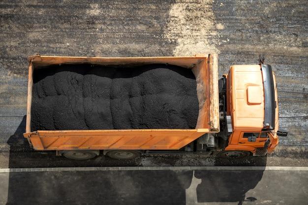 아스팔트 혼합물로 가득 찬 덤프 트럭. 도로 수리 개념입니다. 평면도.