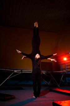 Дуэт акробатов исполняет парный трюк. женщина в гимнастическом комбинезоне и мужчина в спортивной одежде. очень гибкие артисты цирка.