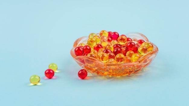 黄色と赤のビタミンa、e、d、オメガ3