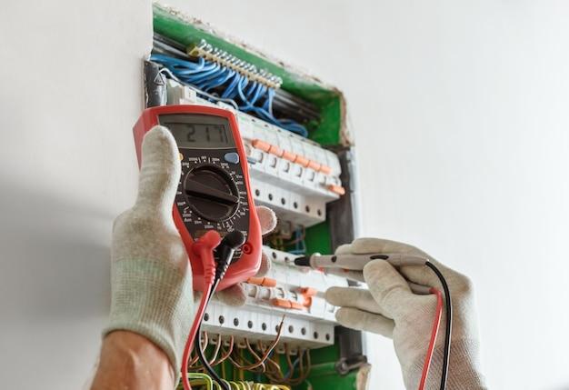 電気技師は、回路ブレーカーの接続の正確さをマルチメーターでチェックしています。