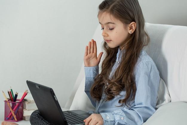 코로나 바이러스 전염병으로 격리 된 초등학생 소녀가 집에서 노트북을 사용하여 원격으로 공부합니다.
