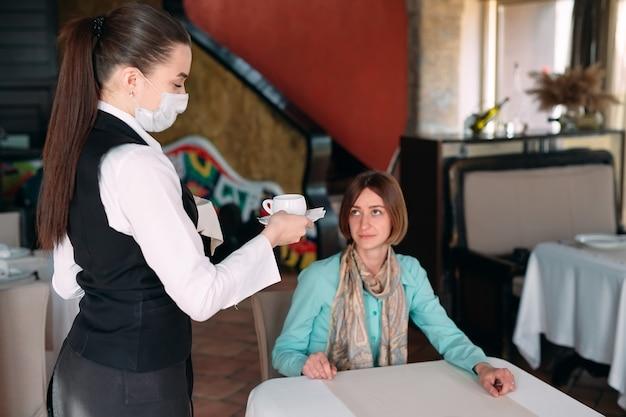 メディカルマスクのヨーロッパ風のウェイターがコーヒーを出します。