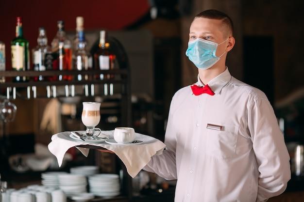 Официант по-европейски в медицинской маске подает кофе латте.