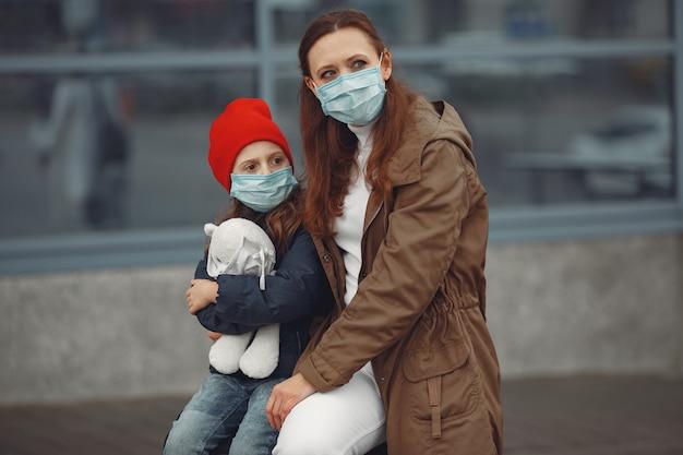 娘と一緒に人工呼吸器を装着しているヨーロッパ人の母親が建物の近くに立っています。
