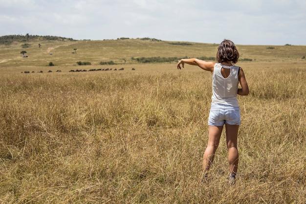 Европейская туристка, наслаждающаяся в национальном парке масаи мара животными на свободе в саванне. кения, африка