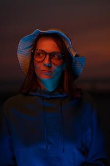 夕焼け空を背景に帽子をかぶったネオンの光に照らされたヨーロッパの女性