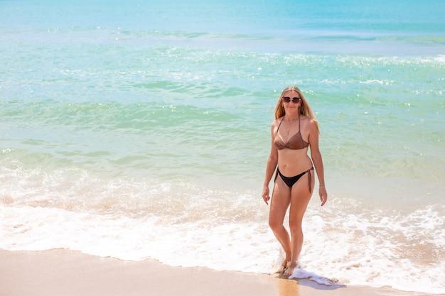 水着姿の長いブロンドの髪を持つヨーロッパの女性は、紺碧の海を背景に砂浜の海辺を歩きます。海岸での夏休み、旅行、観光。