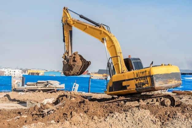 굴착기 불도저는 흙을 파고 건설 현장에 이온을 삽질합니다.
