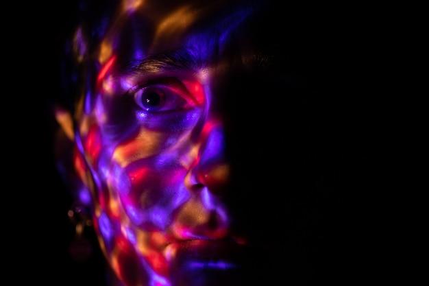 밝은 램프의 밝은 색 반점으로 덮인 어둠의 얼굴 램프의 색 섬광