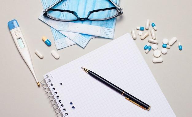 フェイスマスク、丸薬、電子体温計、黒い縁の眼鏡、ノートとペンが灰色の背景に横たわっています。医療の概念