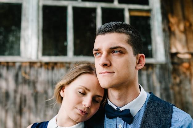 座っていると、木造の古い家の近くにキス若いカップルの顔