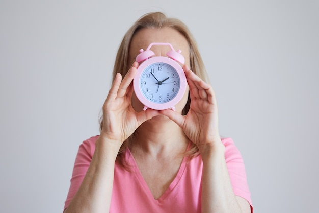 灰色の背景に目覚まし時計を手にしたピンクのシャツを着た女性の顔のない画像。