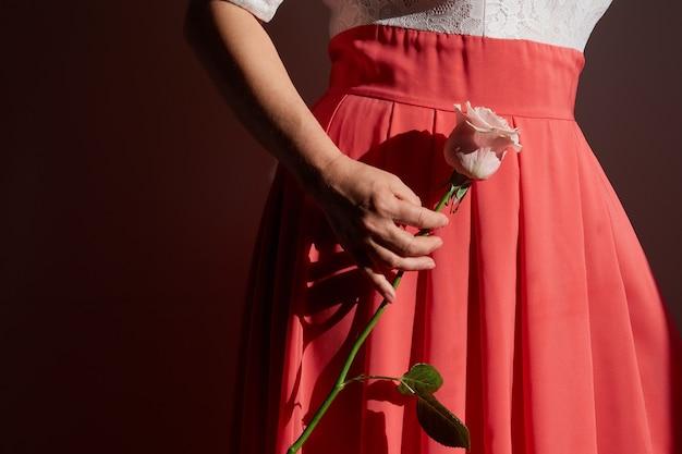 장미를 들고 극적인 빛으로 빨간 드레스를 입은 여성의 얼굴없는 이미지. 발렌타인 데이, 생일, 국제 여성의 날.
