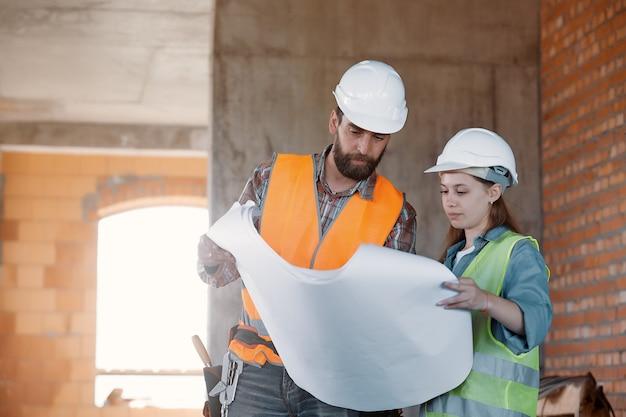 공장 노동자와 엔지니어가 검사를합니다. 작업 계획을 논의하는 생산 라인에 공장 노동자와 비즈니스 여성