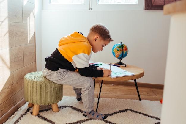 Рисует светловолосый мальчик. чтобы подготовиться к школе. на столе есть глобус