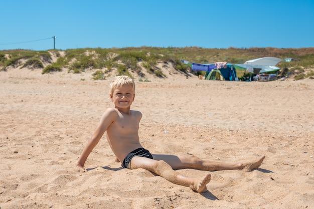 머리 불공평 한 소년이 바다의 모래 위에 앉아 밝은 태양을 바라보며 눈을 가늘게 뜨고 있습니다.