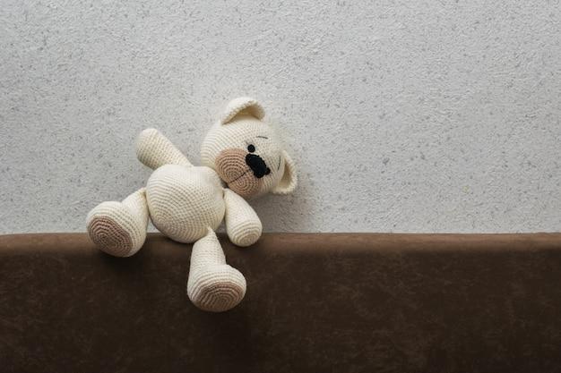 明るい壁に向かってソファに倒れた白いニットのクマの子。美しいニットのおもちゃ。