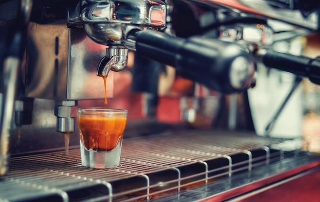 컵에 떨어지는 커피 한 방울. 커피 머신에서 커피를 준비합니다.