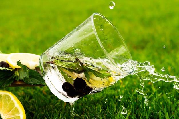 Падающий стакан газированной воды или лимонада с лимоном, черной смородиной и листьями мяты на фоне травы. вода с брызгами и каплями течет из стакана