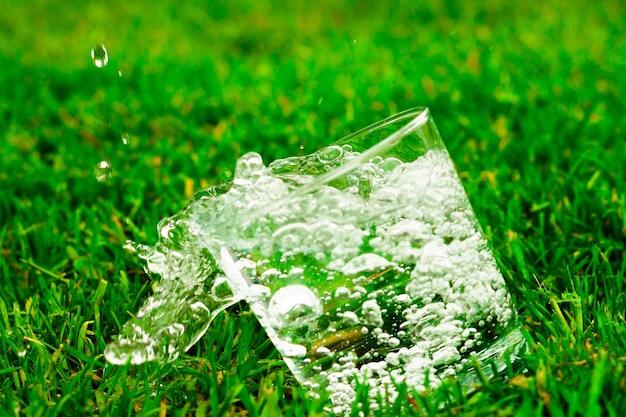Падающий стакан воды или лимонада на фоне травы. из стакана льется вода с брызгами и каплями.
