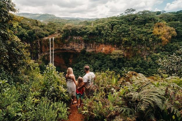 モーリシャス島のシャマレル公園の滝の近くの崖の端に、家族、男性、女性、娘が立っています。