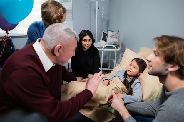 병원을 방문하는 동안 어린 소녀를 위로하는 가족.