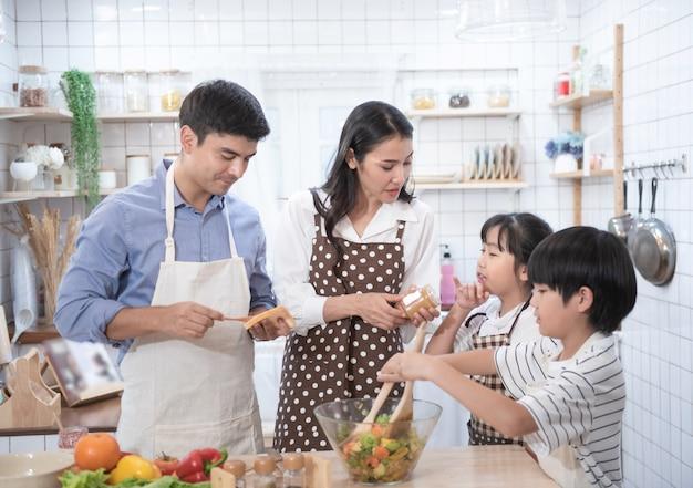 台所で一緒に料理をする家族