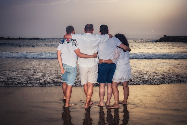 Семья сзади они смотрят на горизонт в море на закате