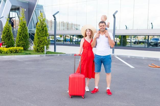 가족이 여행이나 휴가를 가는데, 행복한 백인 엄마, 아빠, 아들이 빨간 가방과 모자를 들고 공항에 있다