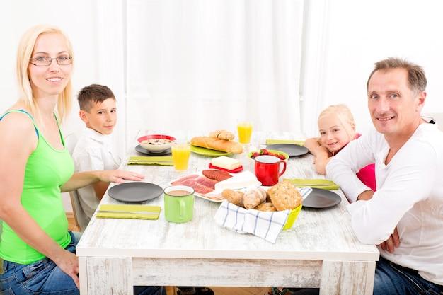 家で朝食をとっている家族。