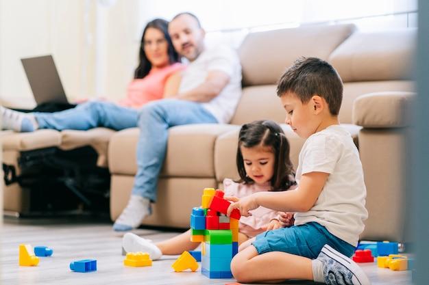 リビングルームの家族、コンピューターを使ってテレワークをする両親、床で遊ぶ子供たち