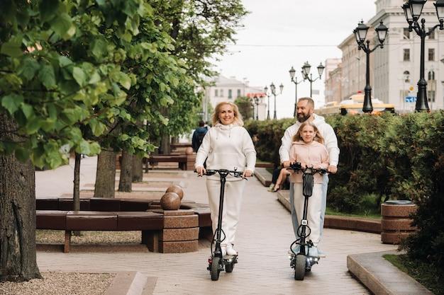 흰 옷을 입은 가족이 도시에서 전기 스쿠터를 타고 야외 활동을합니다.