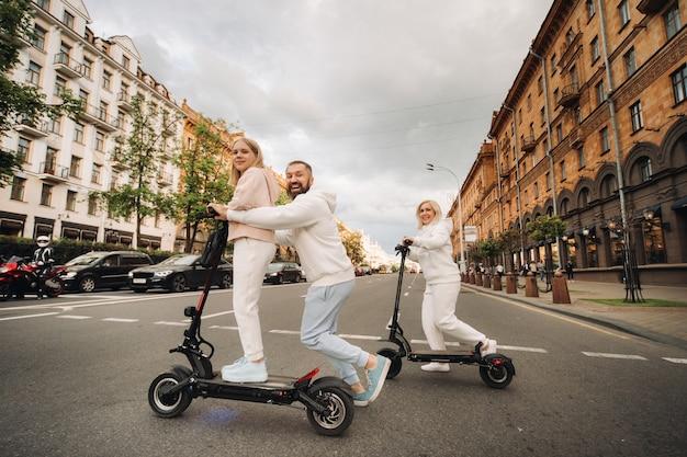 흰 옷을 입은 가족이 도시에서 전기 스쿠터를 타고 야외 활동