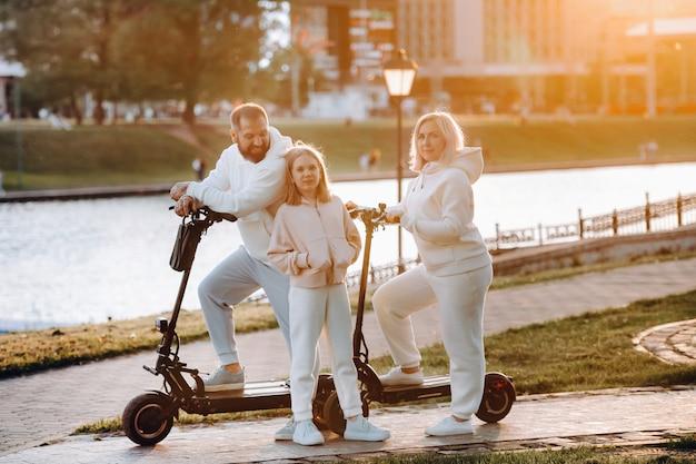 흰 옷을 입은 가족이 일몰에 전기 스쿠터를 타고 도시에 선다.