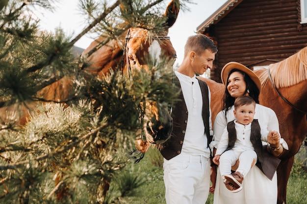 Семья в белых одеждах с сыном стоят возле двух красивых лошадей на природе. стильная пара с ребенком и лошадьми.