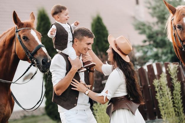 息子と一緒に白い服を着た家族は、自然界の2頭の美しい馬の近くに立っています。子供連れのおしゃれなカップルを馬で撮影。