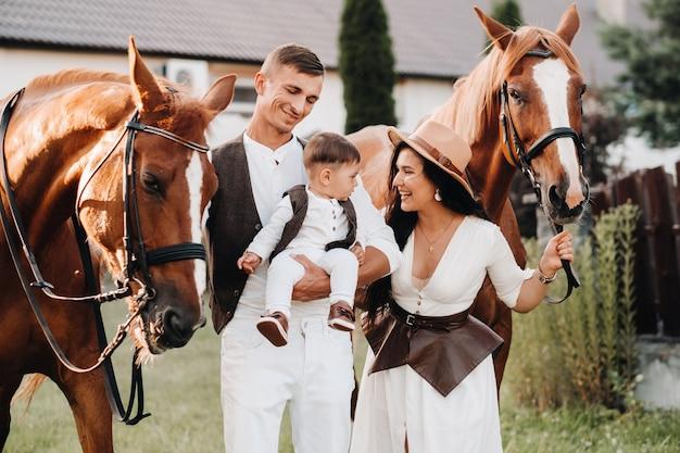 흰 옷을 입은 가족과 아들이 자연 속에서 아름다운 말 두 마리 옆에 서 있습니다. 아이를 안고 있는 세련된 커플이 말과 함께 사진을 찍고 있다