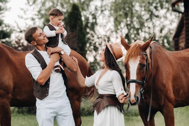 Семья в белых одеждах с сыном стоят возле двух красивых лошадей на природе. стильная пара с ребенком фотографируются с лошадьми