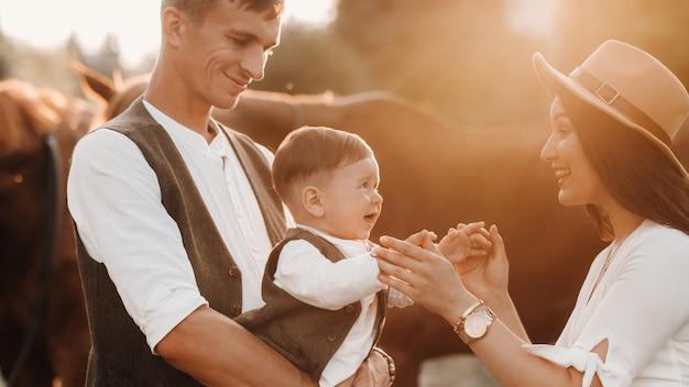 Семья в белых одеждах с сыном стоят возле двух красивых лошадей на природе.