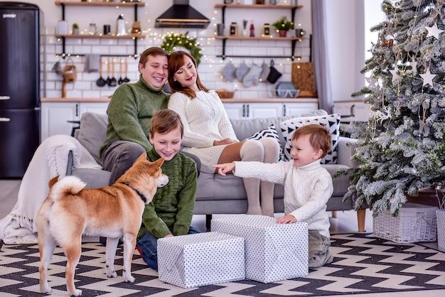 Семья из четырех человек сидит у елки, распаковывает подарки. дети держат завернутые подарки, играют с собакой сиба-ину. счастливые люди встречают новый год.