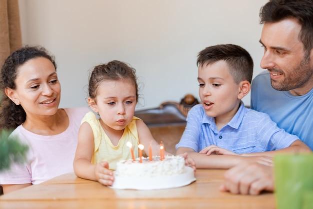 4명의 가족, 두 명의 부모, 두 명의 자녀가 가족 서클에서 어린 소녀의 6번째 생일을 축하하고 케이크에 있는 생일 초를 불고 있습니다.