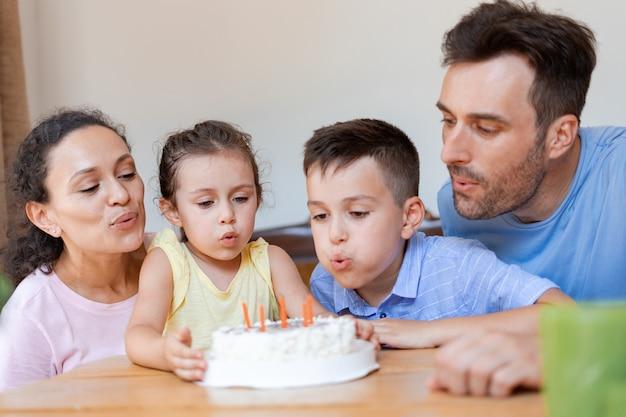 4명의 가족, 두 명의 부모, 두 명의 자녀가 가족 서클에서 어린 소녀의 6번째 생일을 축하하고 생일 소녀가 케이크의 초를 끄는 것을 돕습니다.
