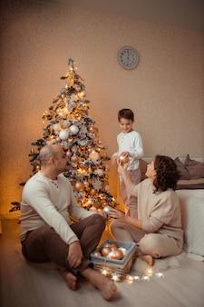 Семья с ребенком дома в спальне у кровати возле елки.