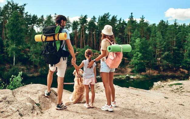 バックパックとラブラドール犬を連れた家族が岩だらけの頂上に立って、川と森を見ています。キャンプ、旅行、ハイキング。