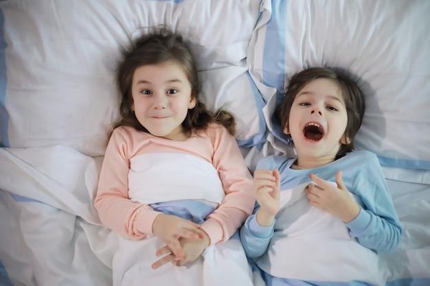 크리스마스 휴가 기간 동안 이불 아래 침대에서 즐거운 시간을 보내는 아이들이 있는 가족.