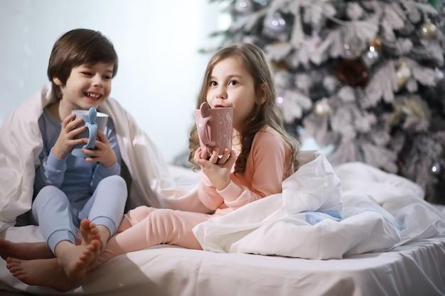 크리스마스 휴가 기간 동안 이불 아래에서 침대에서 즐거운 시간을 보내는 아이들이 있는 가족